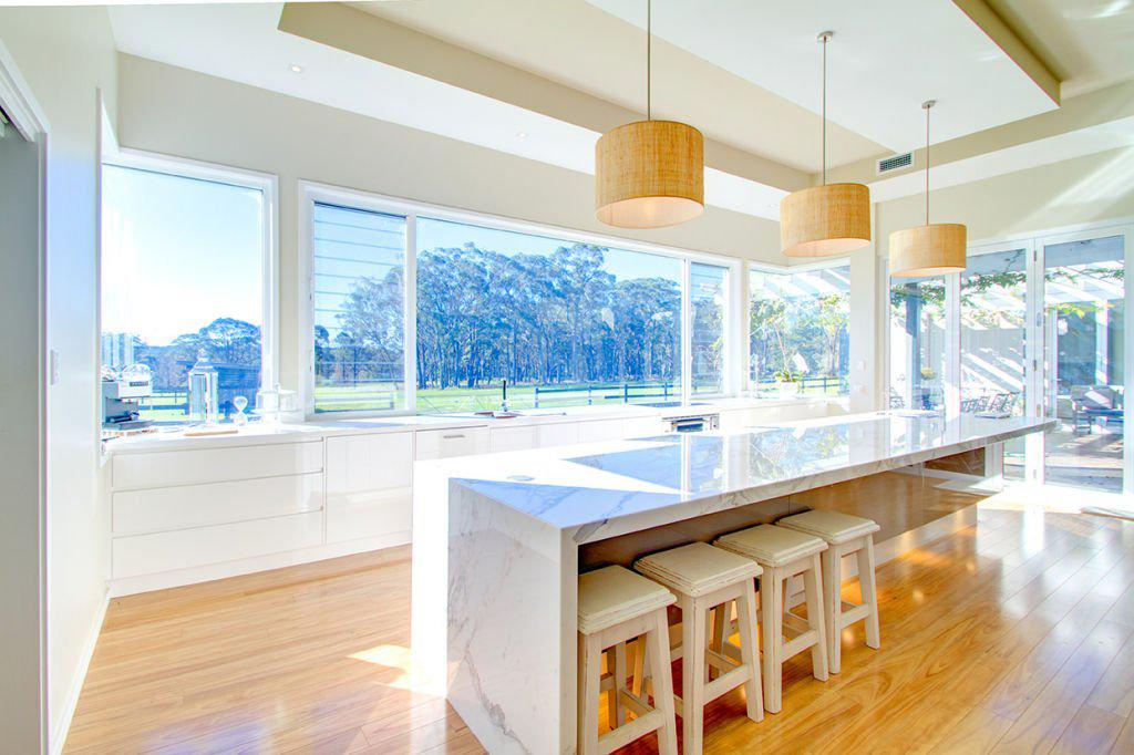 contemporary open kitchen with breakfast bar facing countryside