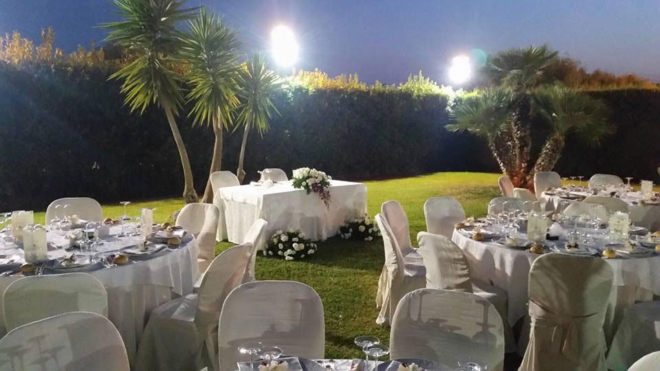 Dei tavoli in un prato con delle palme e luci accese