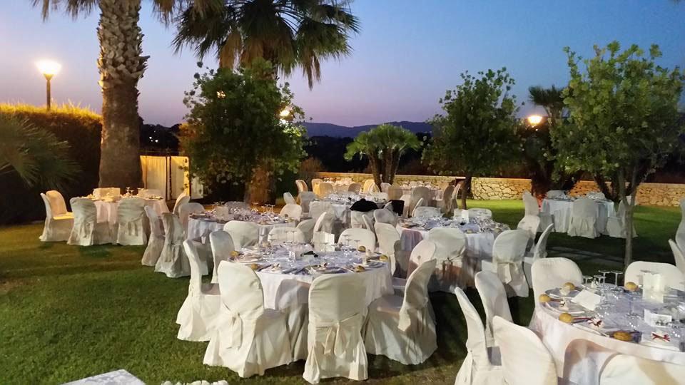 Dei tavoli in un prato con delle palme, luci accese e vista delle colline