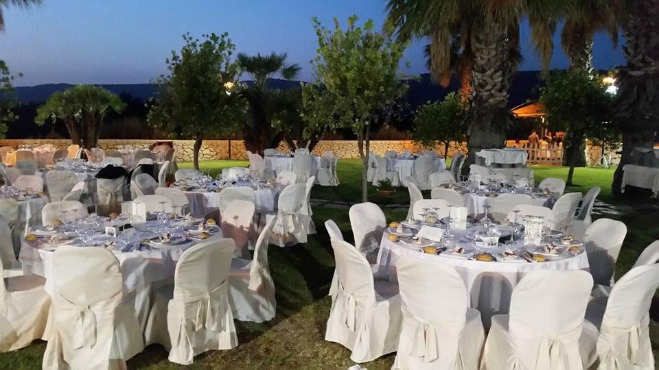 Dei tavoli apparecchiati in un prato con delle palme, luci accese e vista delle colline
