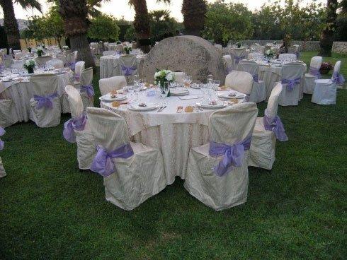 Dei tavoli con delle tovaglie bianche e sedie con copri sedie di color bianco con dei fiocchi