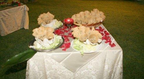 Un tavolo con un lumino rosso, petali di rosa e dei dolci