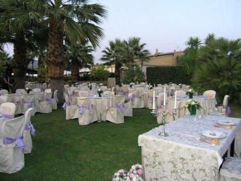 Dei tavoli con delle tovaglie bianche e sedie con copri sedie di color bianco con dei fiocchi di color viola