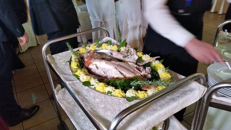 Un cameriere davanti a un carrello con un vassoio con dei filetti di pesce