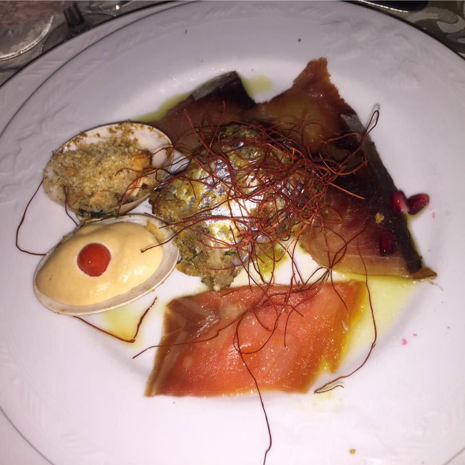 Un piatto con un misto di carpaccio di  pesce