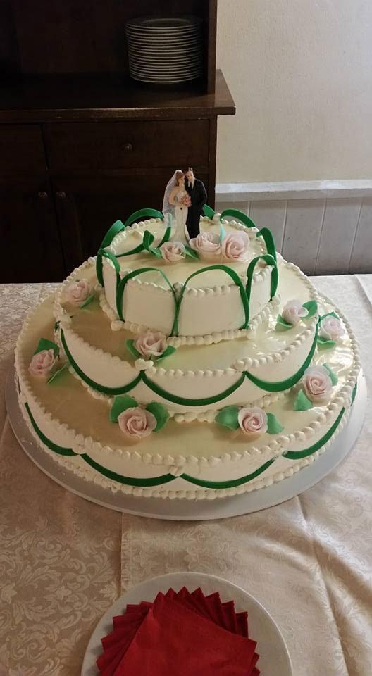 Una torta decorata con dei nastri di color verde e dei pupazzetti di una coppia
