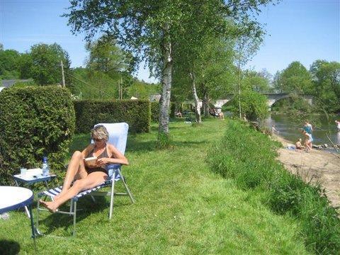 Vrouw leest ontspannen een boekje op de familiecamping in de Belgische Ardennen