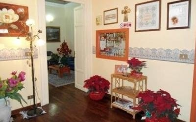 una stanza con delle cornici al muro e dei vasi di fiori