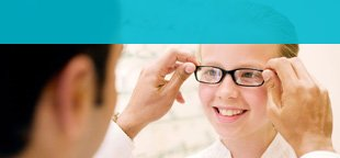 Optician checking glasses on patient for fit in Holywell