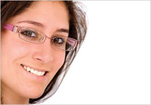 Lady wearing pink rimless glasses in Saunders Opticians, Colwyn Bay