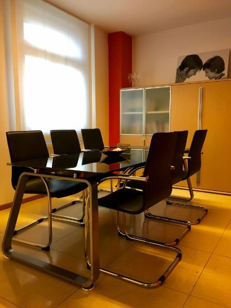 una sala con un tavolo di vetro, sei sedie e un mobile