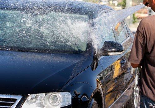 Un uomo mentre lava una macchina nera