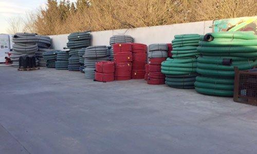 dei grossi tubi di gomma arrotolati di diversi colori all'esterno di un magazzino