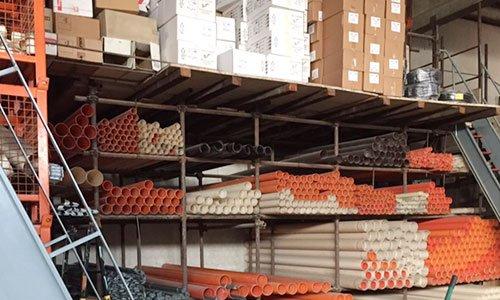 dei tubi di plastica bianchi e arancioni dentro a degli scaffali in ferro e sopra degli scatoloni