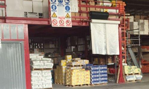 dei bancali di materiale con confezioni di color giallo e blu e sopra un soppalco in ferro color rosso