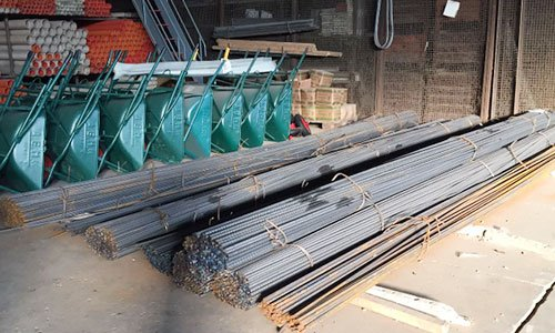 insieme di barre di ferro divise a gruppi e legate e affianco delle carriole verdi