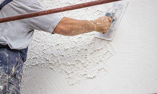 un muratore che utilizza una spatola su un muro fresco di color bianco