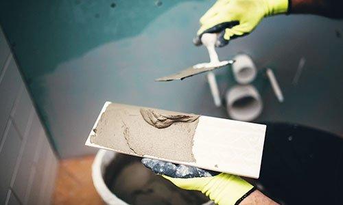 due mani con in mano un ferro con sopra del cemento e dall'altra una spatola