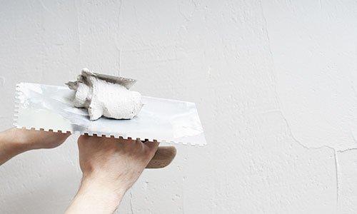 due mani con una spatola dentata e sopra del cemento