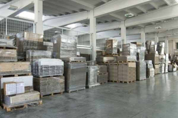 interno del magazzino con bancali di legno e sopra del cartone confezionato con il celofan