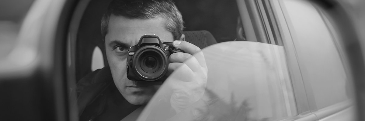 Man Looking through lens of camera