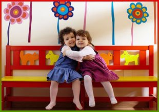 Two small children hugging on colourful bench