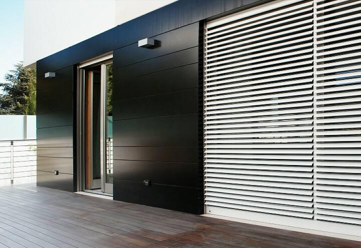 Una porta finestra e una facciata di color nero