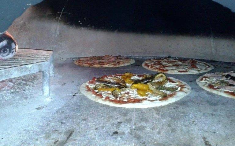 Le pizze stanno cuocendo nel forno a legna