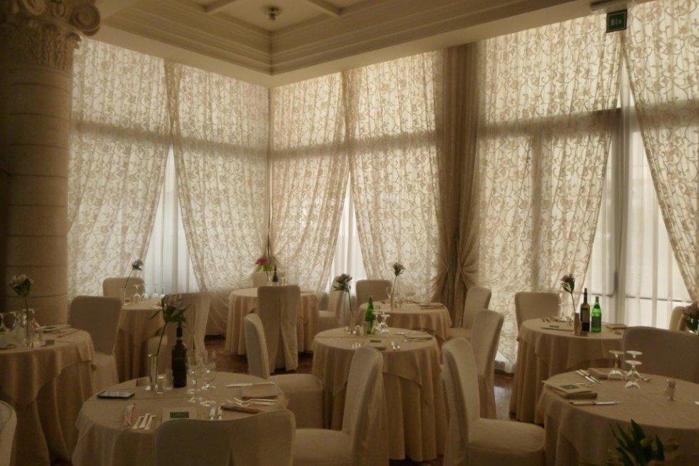 sala ristorante con drappeggi a copertura delle vetrate