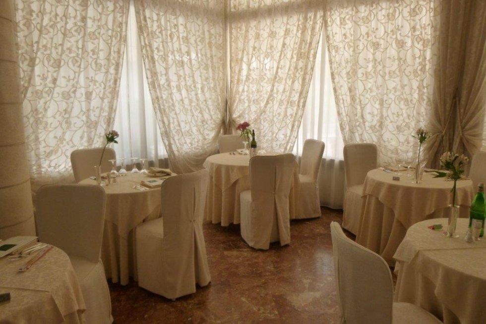 sala ristoro con grandi finestre e drappeggi color crema