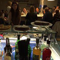 Delle bottiglie di liquore e una ragazza in piedi vicino a una vetrina con sopra delle torte
