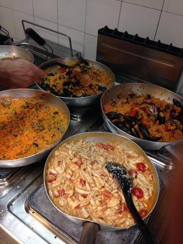 padelle sui fornelli con dentro paella e primi piatti