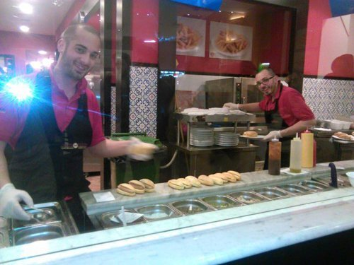 cuochi preparano panini dietro il bancone