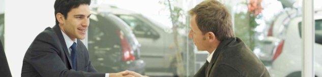 due uomini mentre stringono le mani in uno showroom di auto