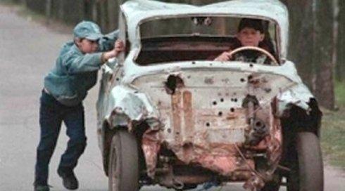 un bambino mentre spinge una macchina rotta
