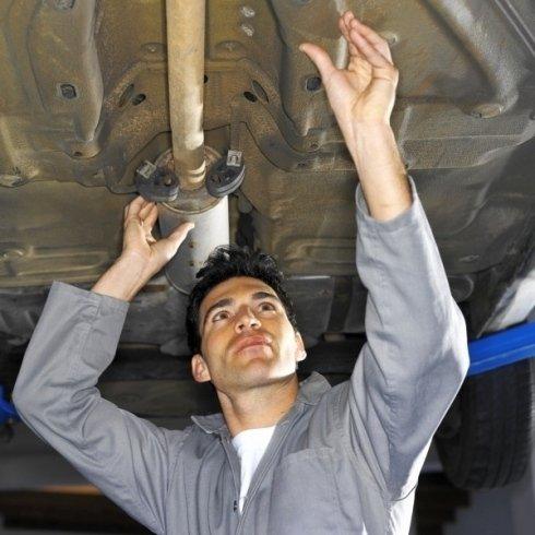un meccanico che controlla il sotto di una macchina