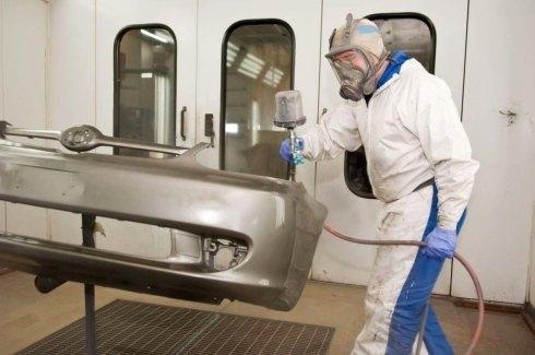 un uomo in tuta bianca che vernicia una carrozzeria di un'auto