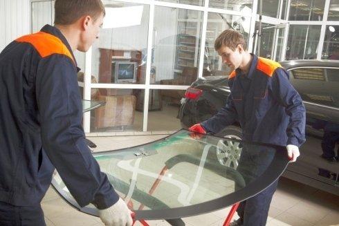 due meccanico con in mano un vetro anteriore di una macchina