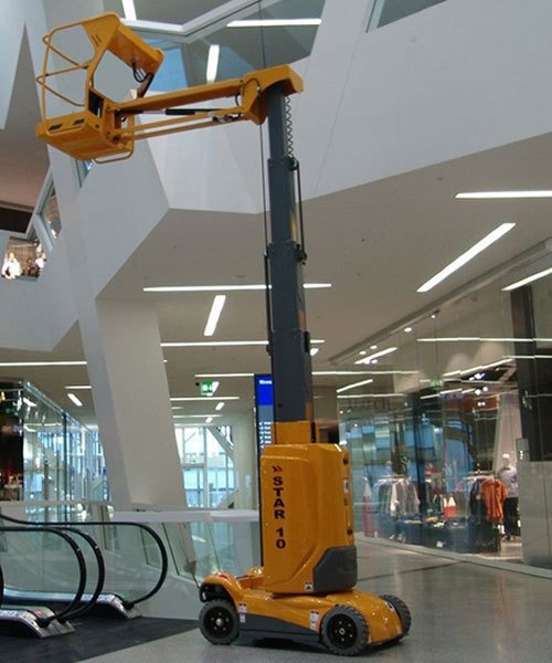 A small cherry picker inside a shopping centre