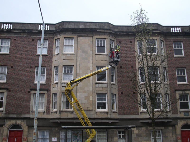 Window cleaners using a large yellow cherry picker