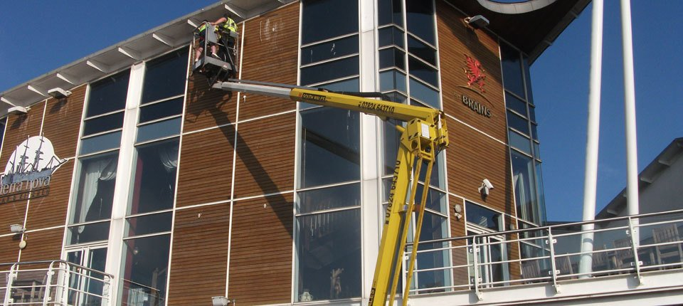 Two men working on a building from a cherry picker