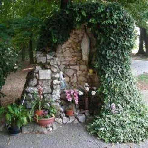 muretto di pietra con dell'edera,una Madonnina e dei vasi di fiori
