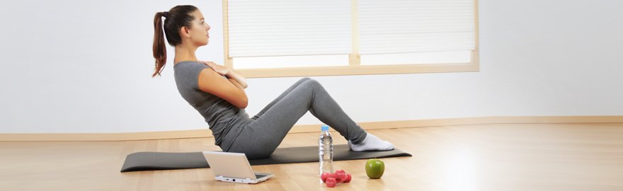 A lady in grey t-shirt and leggings, doing sit-ups on a mat beside a lap top computer, bottle of water and some fruit