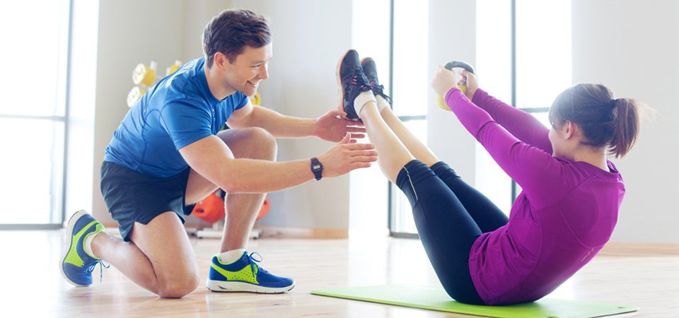A personal trainer working with a young lady doing crunches