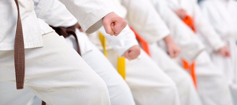 A row of people in white karate clothing with orange or yellow belts