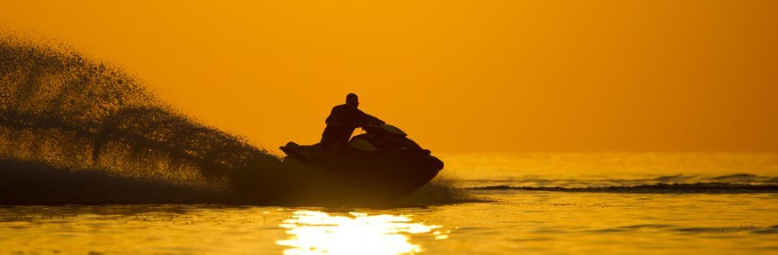 View of the individual during sunset riding the jetski