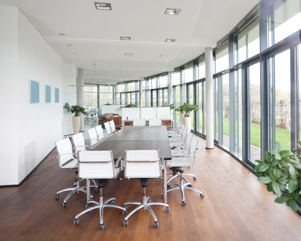 a modern office with white chair and wooden table