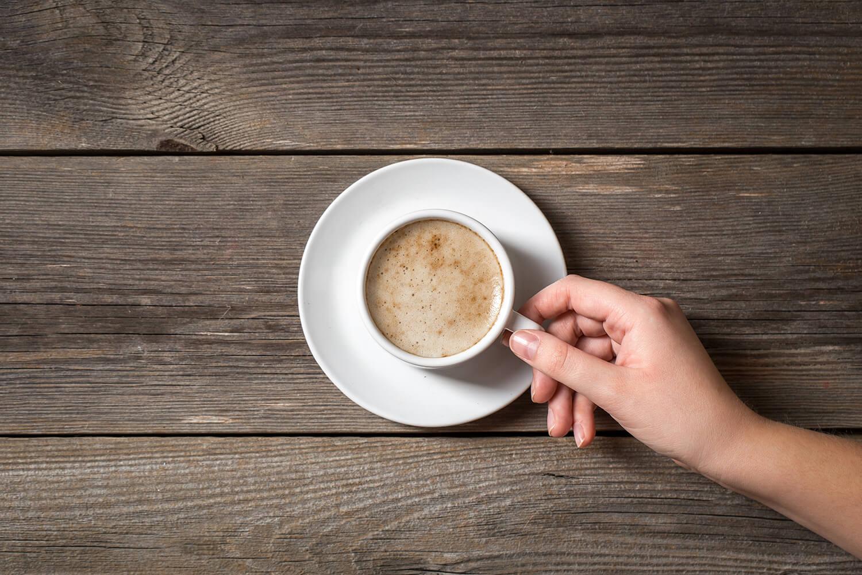 Mano con una tazza di caffè