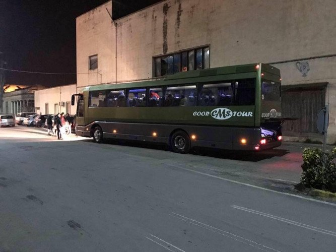 un pullman verde con vetri oscurati con la scritta Coop. CMS Tour