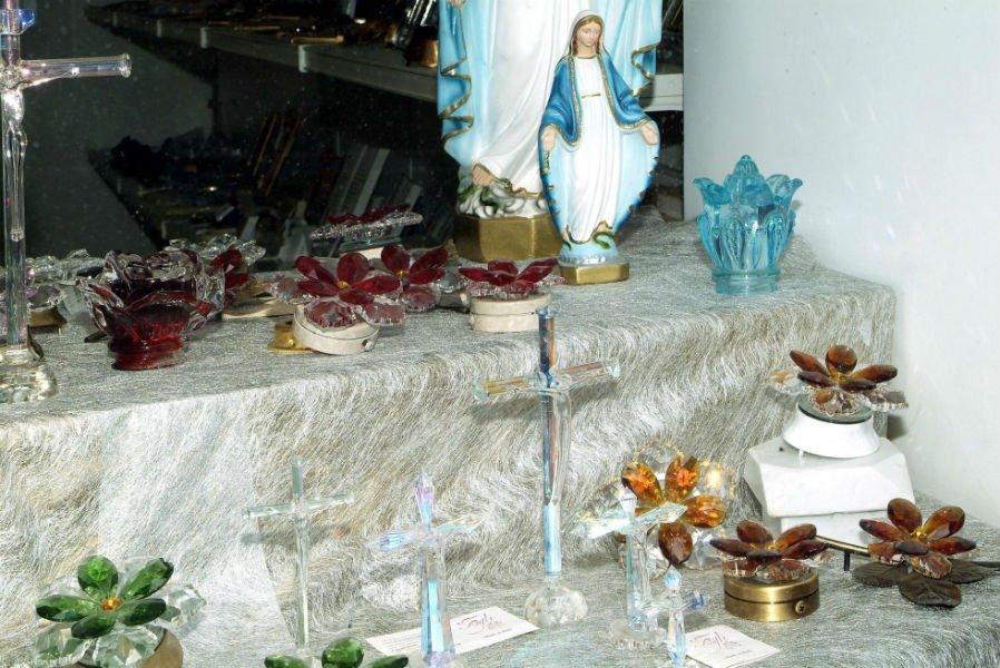 una statuetta della Madonna e dei ceri con dei fiori colorati